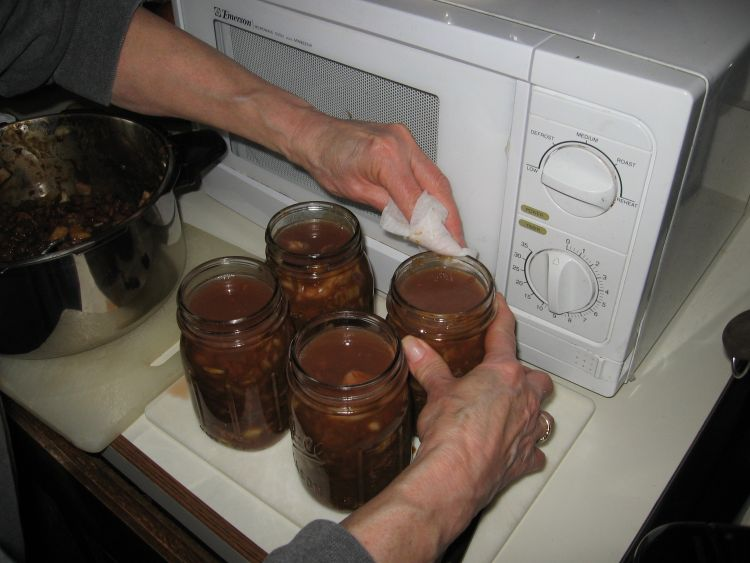 Wiping the tops of the jars